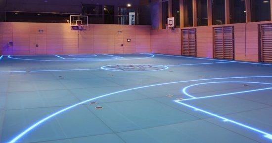 这种地板能够直接在玻璃表面利用可设计的LED照明来显示界线、视频信息或者特定的用词   这种玻璃地板被称作ASB玻璃地板,它的材料使用了一种陶瓷工艺进行了一系列的处理,达到了类似于标准木质地板的弹性和摩擦水平。除此之外,玻璃表面经过钝化处理后大大减少了反射效果,以免运动员注意力分散。这种处理也碰巧隐藏了运动过程中导致的任何划伤,而且玻璃地板能够定制成任何颜色。地板的颜色以后也可以更换,这对于采用不同颜色的运动团队来说是非常理想的。除此之外,玻璃地板是由轻量级铝制框架支撑,而且这种框架内也包含有LED灯光